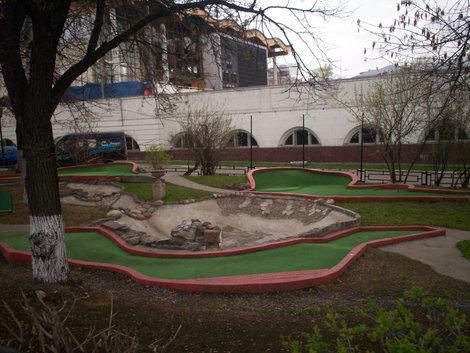 Поле для мини-гольфа; бассейн — на заднем плане