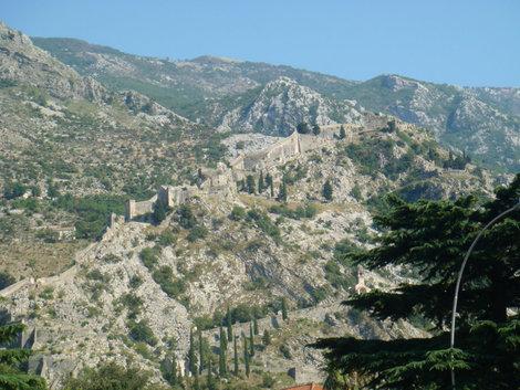 Вид на лестницу, ведущую на крепость на горе. Справа вверху видна красноватая точка — флаг Черногории