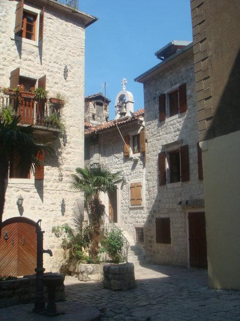 Которский дворик с церковным колоколом и колонкой на первом плане слева