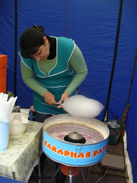 Творительница сахарной ваты как добрая фея наматывает тонкую паутинку на палочку