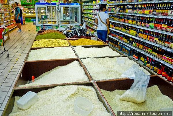Рис и крупы продаются на развес. Мы подходим к ящикам. Насыпаем столько риса, сколько нам необходимо, взвешиваем и приклеиваем ценник к пакетику.