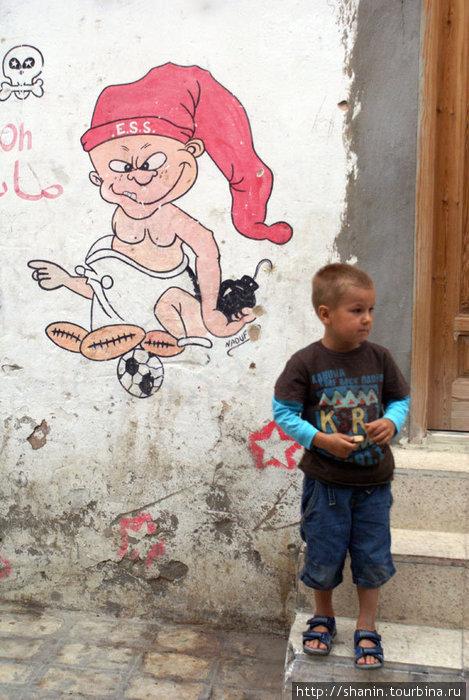 Ребенок и детский рисунок на стене дома в медине