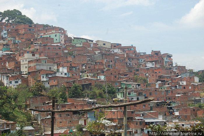 Одинаковые домики из красного кирпича жмутся к склонам горы.