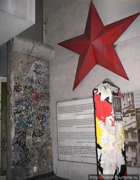 Пограничный столб с бывшей границы ГДР и фрагмент стены на заднем плане