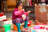 Эта милая китайская женщина взвешивает рыбью голову. У нее в руках очень распространенные среди местных рыночных торговцев весы. Простые и гениальные, как и многие китайские изобретения.