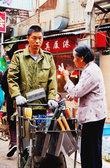 А этот мужчина ножи продает. Он катит свою тележку вдоль рыночных улиц и звонко лязгает одним лезвием об другое, при этом кричит что-то гортанным голосом на местном диалекте – минаньхуа.