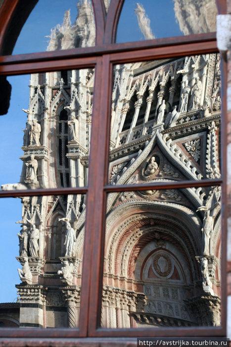отражение сиенского Дуомо в окне