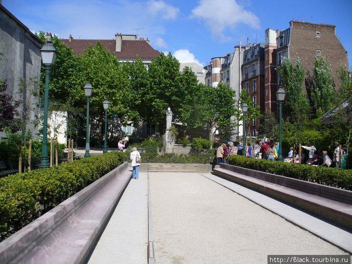 Площадка для игры в петанк у статуи Святого Дионисия