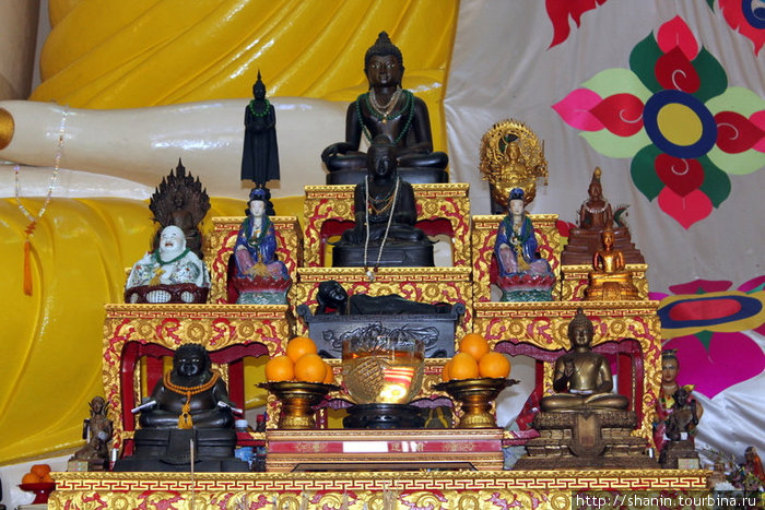 Алтарь со статуэтками богов у ног сидящего Будды