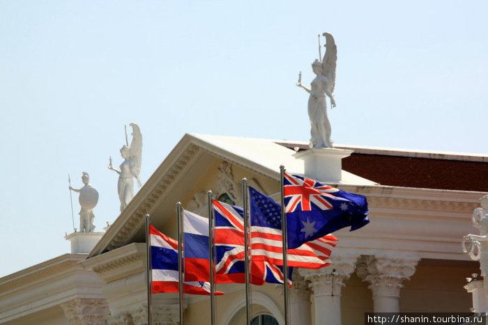 Флаги — включая российский — у гостиницы с камбоджийской стороны погранперехода.