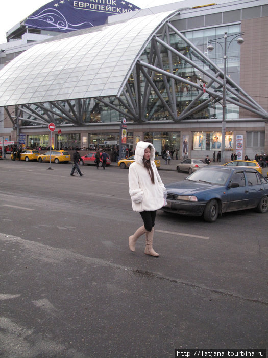 девушка в белом на фоне торгового центра