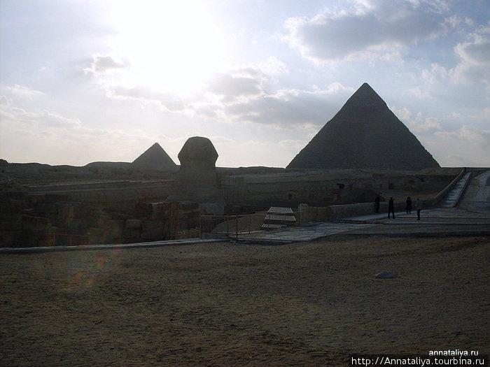 Сфинкс на фоне пирамид и солнца