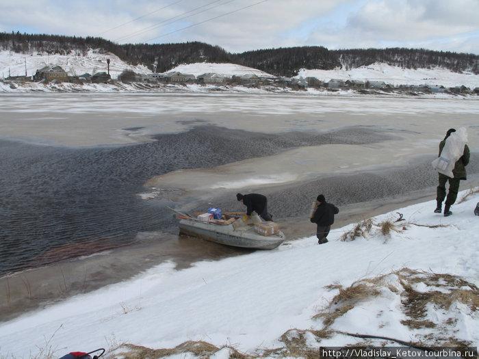 Глава администрации посёлка Верхняя Золотица перевозит на своей лодке почту и гостей с вертолётной площадки на другую сторону реки, в посёлок.