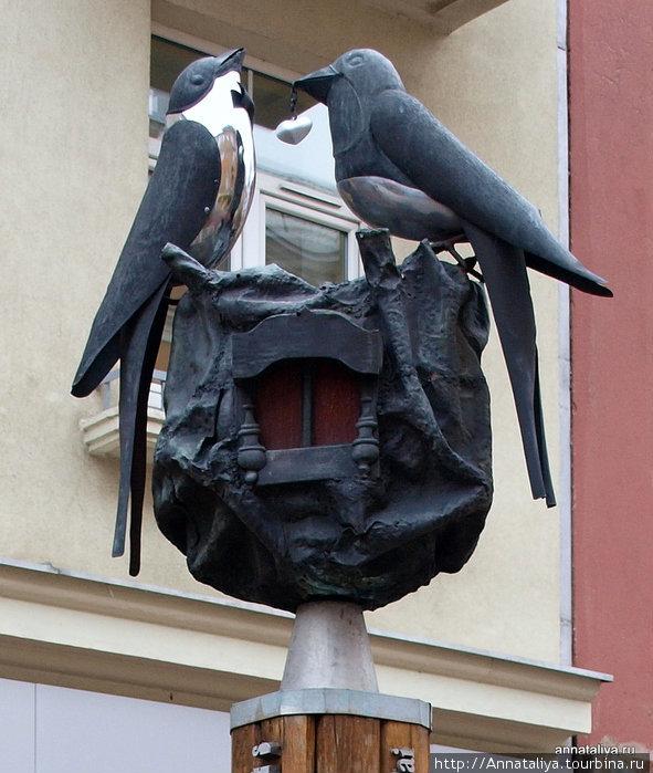 Столбик с птичками и с ювелирным украшением напротив ювелирного магазина