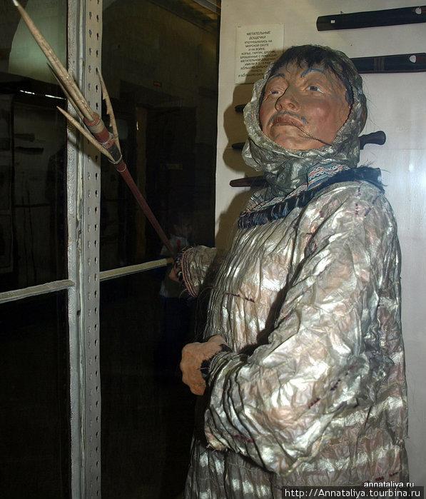 Алеут-охотник в промысловой одежде из кишок морских животных.