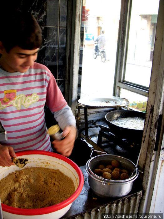 Вот так молодой мальчишка, сын хозяина кафе, лихо стряпает фалафель.