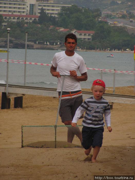 малыш помогает бич-бою убирать пляж :)