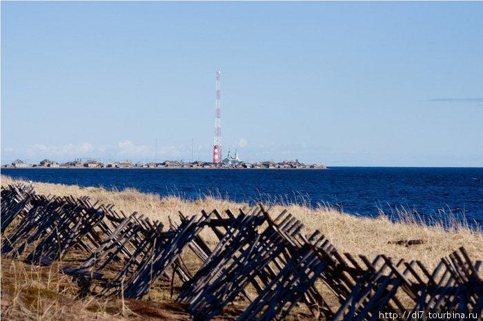 Довольно длительное время дорога идет по берегу Белого моря. Чтобы зимой ее на заметало пургой, ставят такие вот заборы. На горизонте-пос.Кашкаранцы-жилье пограничников, маяк