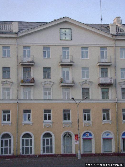 На фасаде здания с ажурными арками окон на первом этаже часы отчетливо показывали 23:54