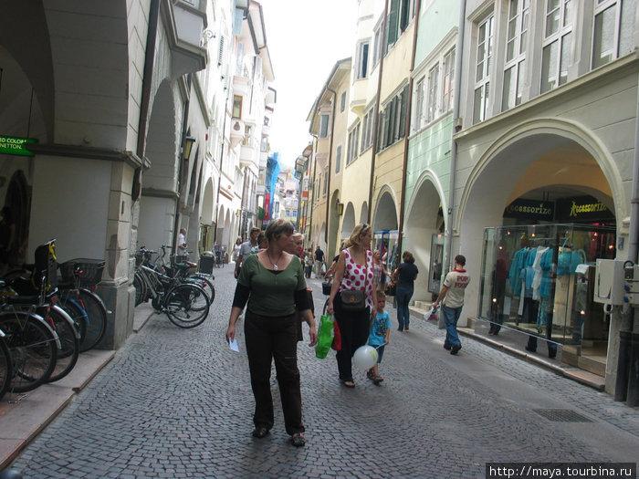 за ней улица — галерея, узенькая дорога для пешеходов и велосипедистов,  тротуары под крышами-арками и магазины