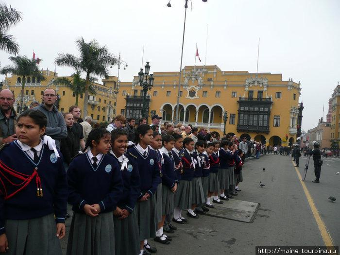 Школьники и туристы через дорогу наблюдают за тасовками караула в президентском дворце.