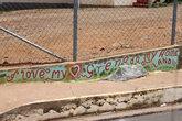 Надпись на заборе школы:-Я люблю мою Гренаду, мою землю