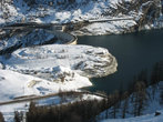 Озеро Ле Лак и дамба, защищающая от воды деревушки внизу. По дамбе идет дорога.