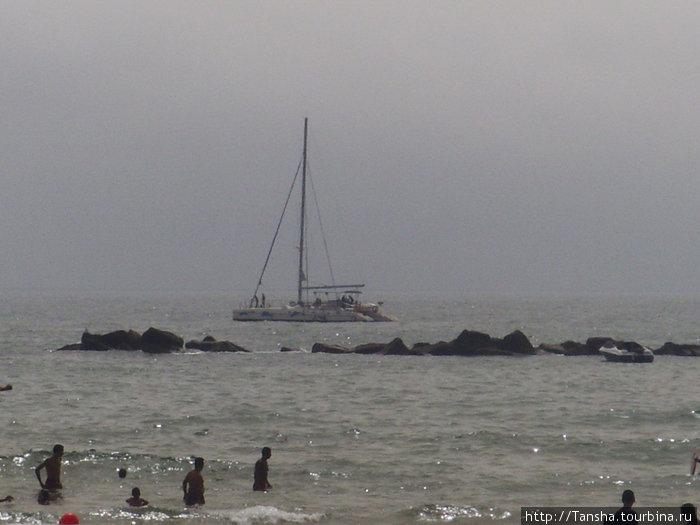 Яхта в океана недалеко от камней, выступающих из воды. Особенность океана -частые прилывы и отливы. Так что \