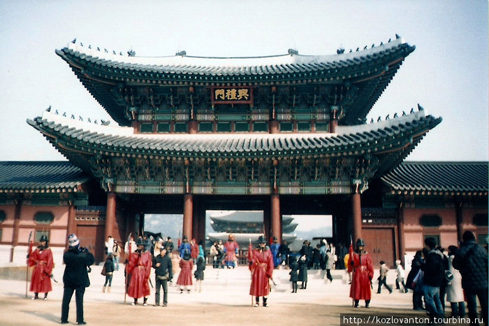 Живописные охранники и многочисленные туристы перед центральным входом в Кёнбоккун. За воротами виднеется главный павильон дворца — Кынчжончжон.