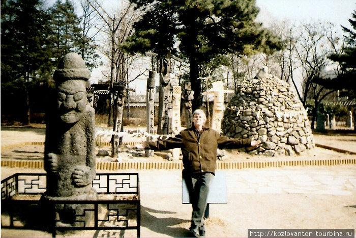 Шаманские столбы (сзади от меня) и божок Тольхарубан с острова Чечжудо (слева).