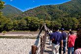 Толпы переправляются через реку Сё-гава от остановки в деревню