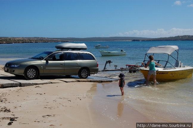 Туристы грузят свой катер на прицеп