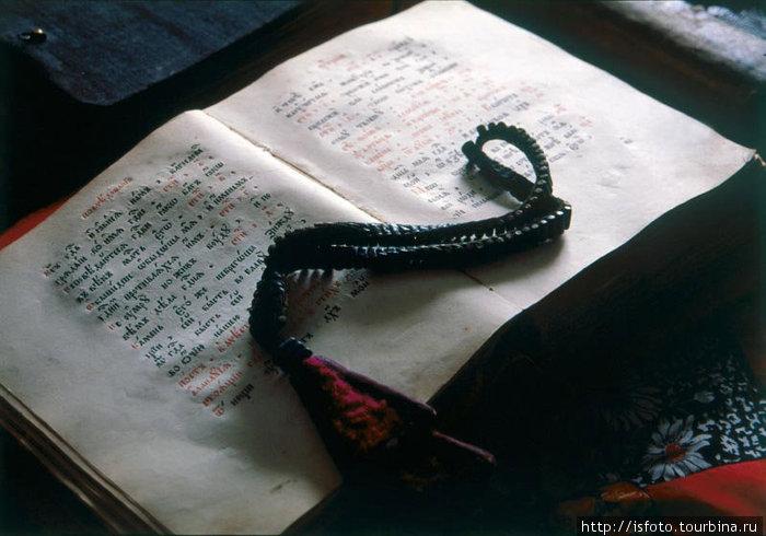 Древняя книга со священным писанием и староверческие четки.