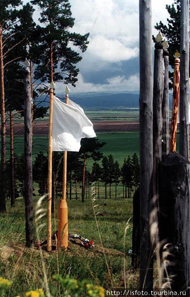 Старинное бурятское кладбище. Вместо плит и надгробий здесь втыкают шест с флагом и буряскими символами — полумесяц, солнце и огонь.