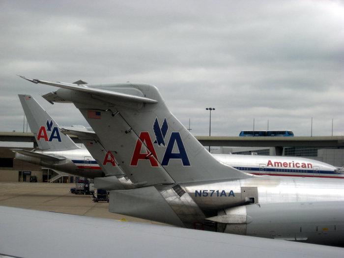 Самолеты компании АА (Аmerican Airlines) в Далласе. На эстакаде поезд без машиниста, соединяющий терминалы аэропорта.