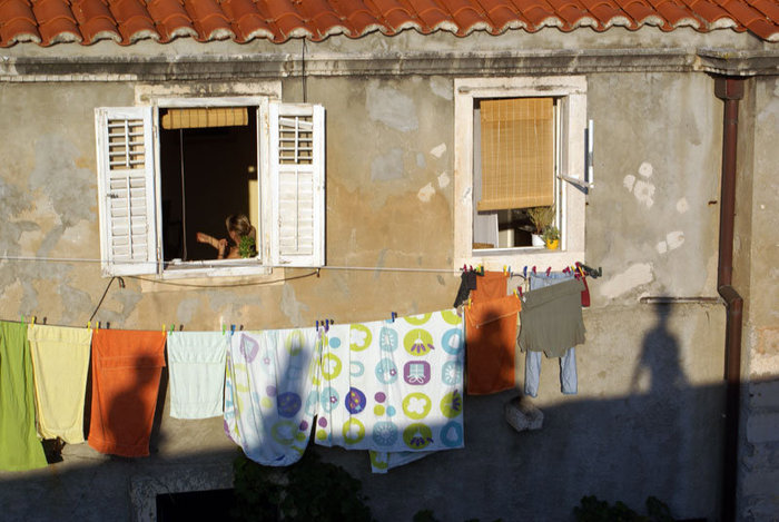 Жизнь напоказ. Тени туристов, проходящих по крепостной стене, на стене жилого дома.