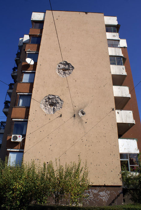 Стены от пуль и снарядов на многоэтажке в Сараево.