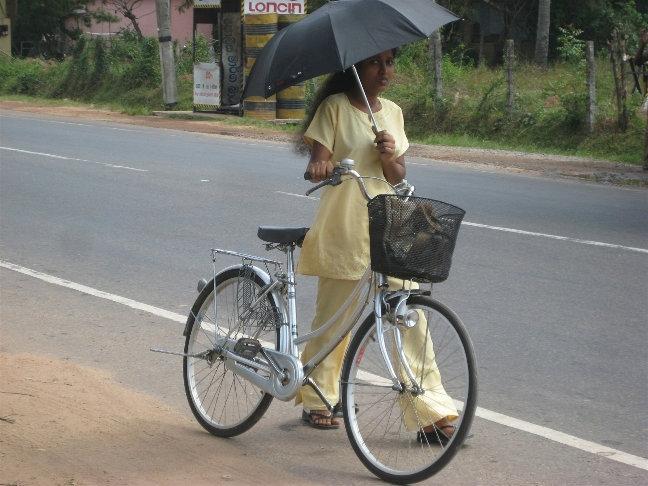 Не думайте, что это прикол — на Шри Ланке в жаркий солнечный день большинство жителей женского пола использует зонт как защиту от солнца. А солнышко, скажу я вам, тут горячее :)